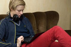 Bild på en ung kille sittade i en soffa med en liten laptop.