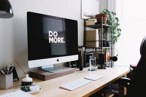 Content writing kräver en arbetsplats med dator och andra investeringar som ska betalas med det som tjänas in. Bild på arbetsplats med en iMac med kringutrustning.