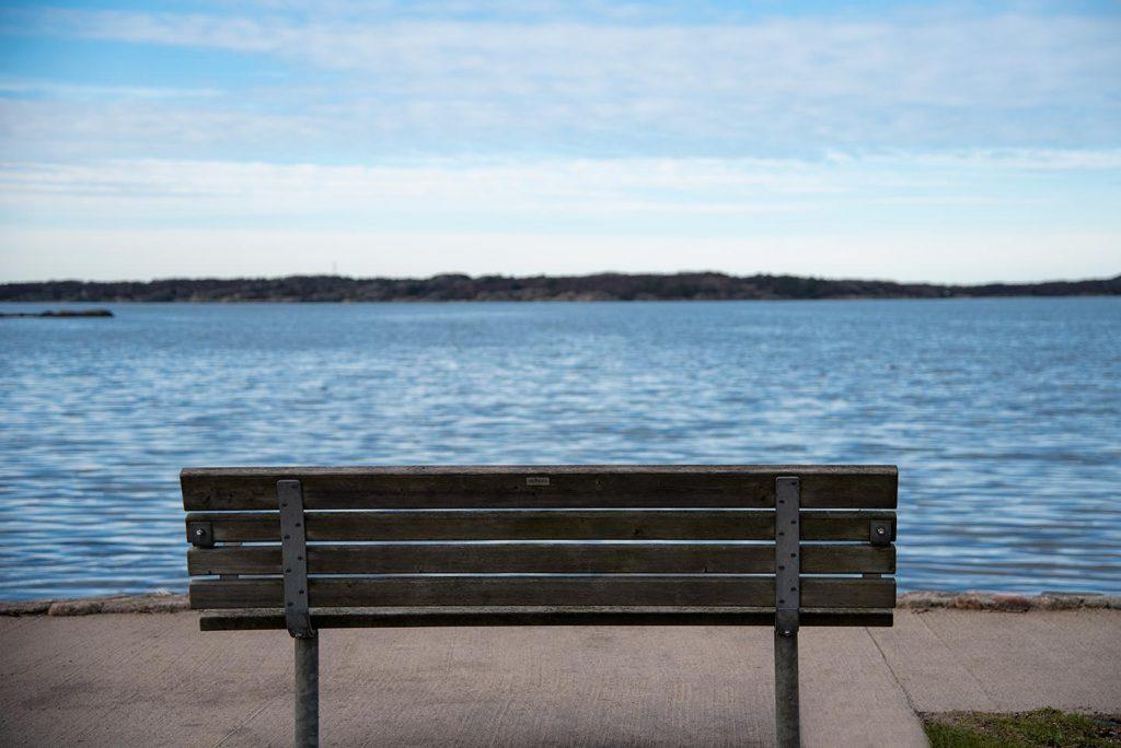 Bild på ryggen på en parksoffa med utsikt över havet.