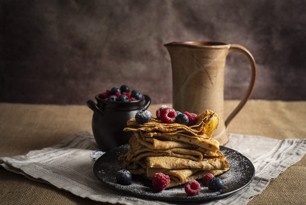 Bild på en tallrik med ihopvikta pannkakor med färska hallon och blåbär strödda över. Bakom står en beige kanna och en svart liten kruka med fler bär.